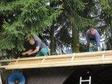 Dobrovolníci na střeše při její opravě